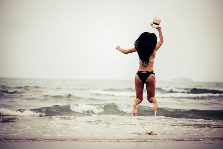 Sea Beach Land One Person Rear View Water Lifestyles Human Arm Horizon Over Water Leisure Activity Limb Full Length Motion Horizon Women Sky Arms Raised Adult Outdoors Human Limb Hairstyle