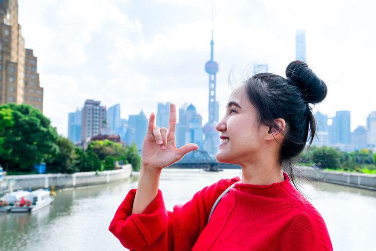 Young woman with arms outstretched against buildings in city