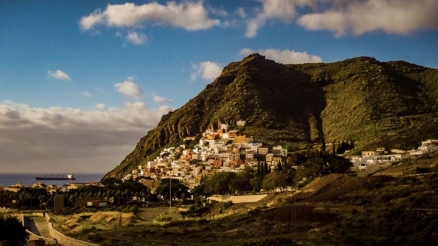 Panoramic Shot Of Townscape By Mountains Against Sky