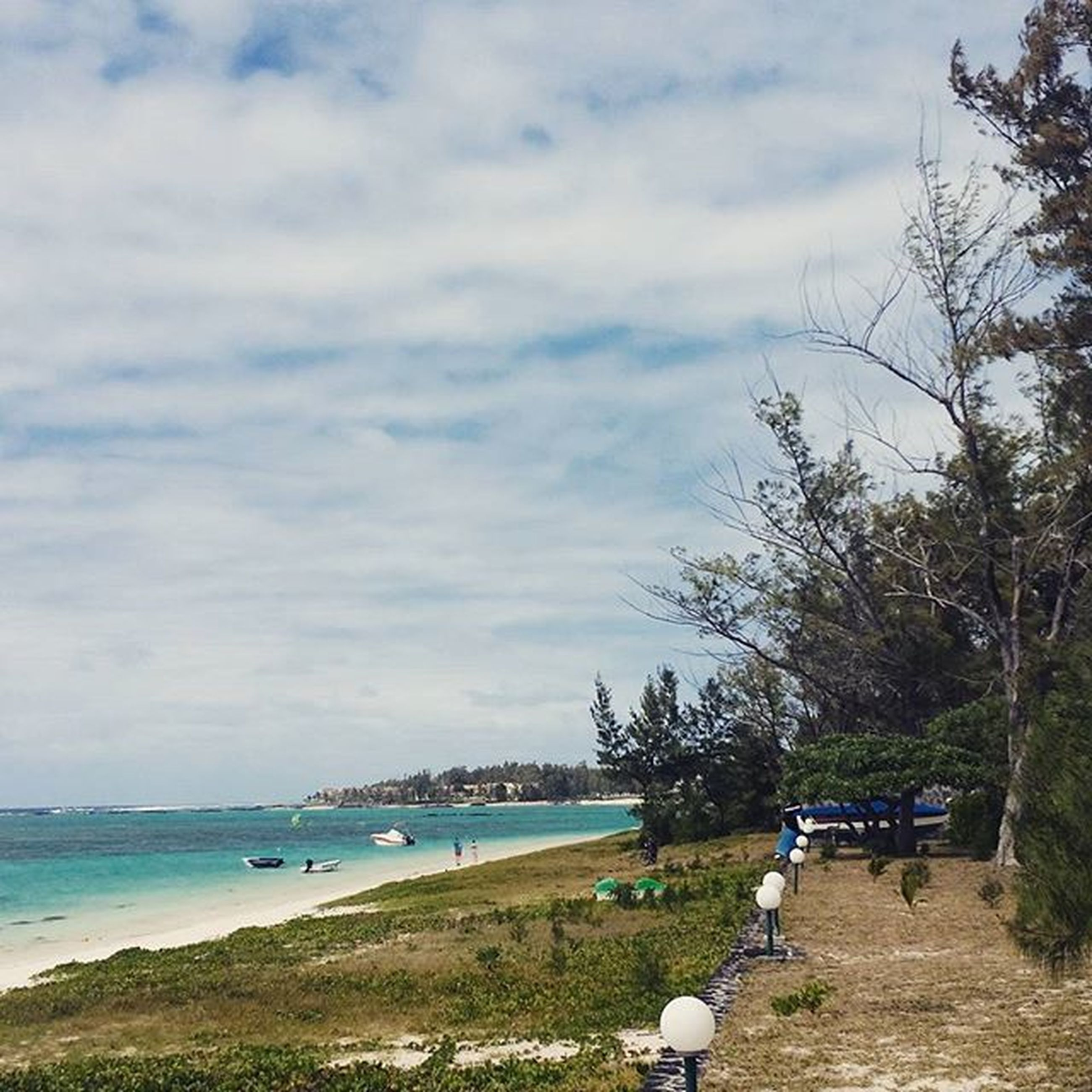 sky, water, sea, beach, cloud - sky, tree, tranquility, shore, tranquil scene, scenics, nature, cloud, beauty in nature, cloudy, sand, horizon over water, incidental people, day, outdoors, coastline