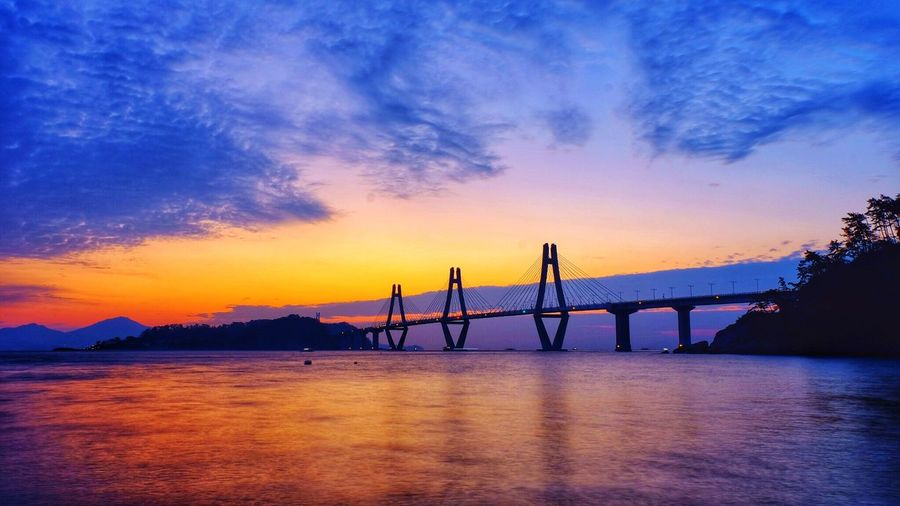 Bridge over calm sea against sky during sunset