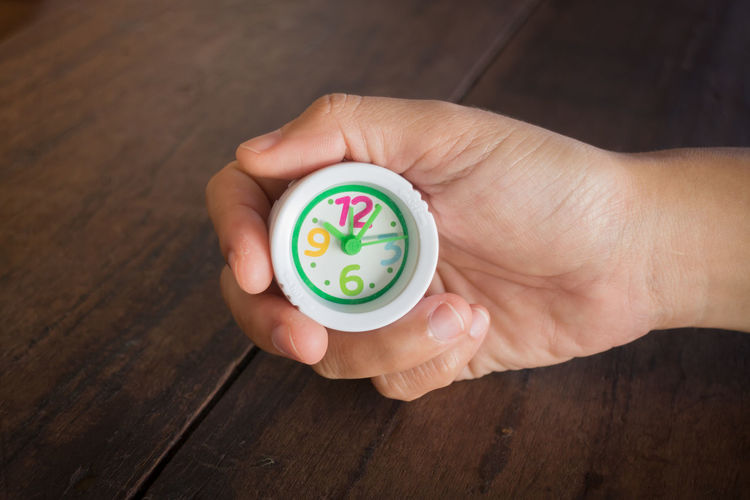 Close-Up Of Human Hand Holding Toy Clock