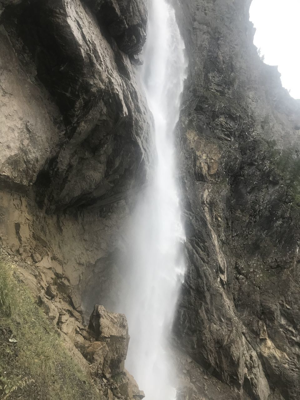 LOW ANGLE VIEW OF WATERFALL AMIDST ROCKS