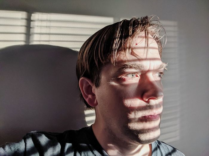 Portrait of young man looking away at home