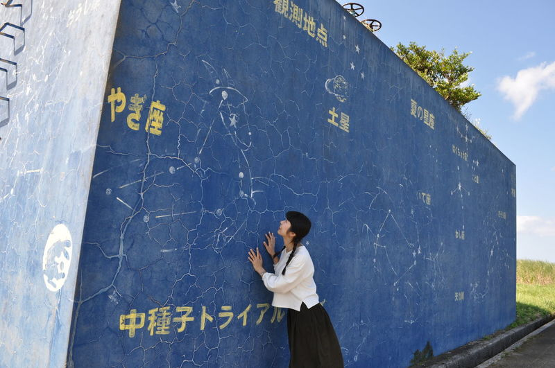 Full length of woman standing by text on wall