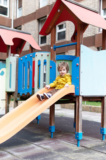 Portrait of boy on playground against building
