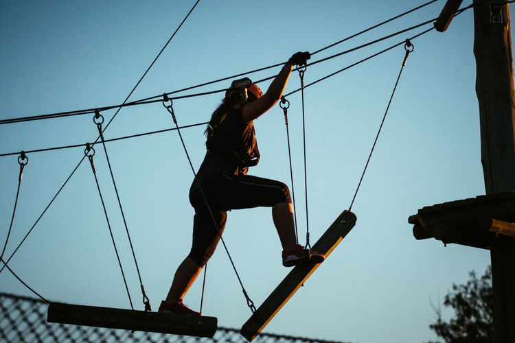 Low angle view of girl walking on rope against sky
