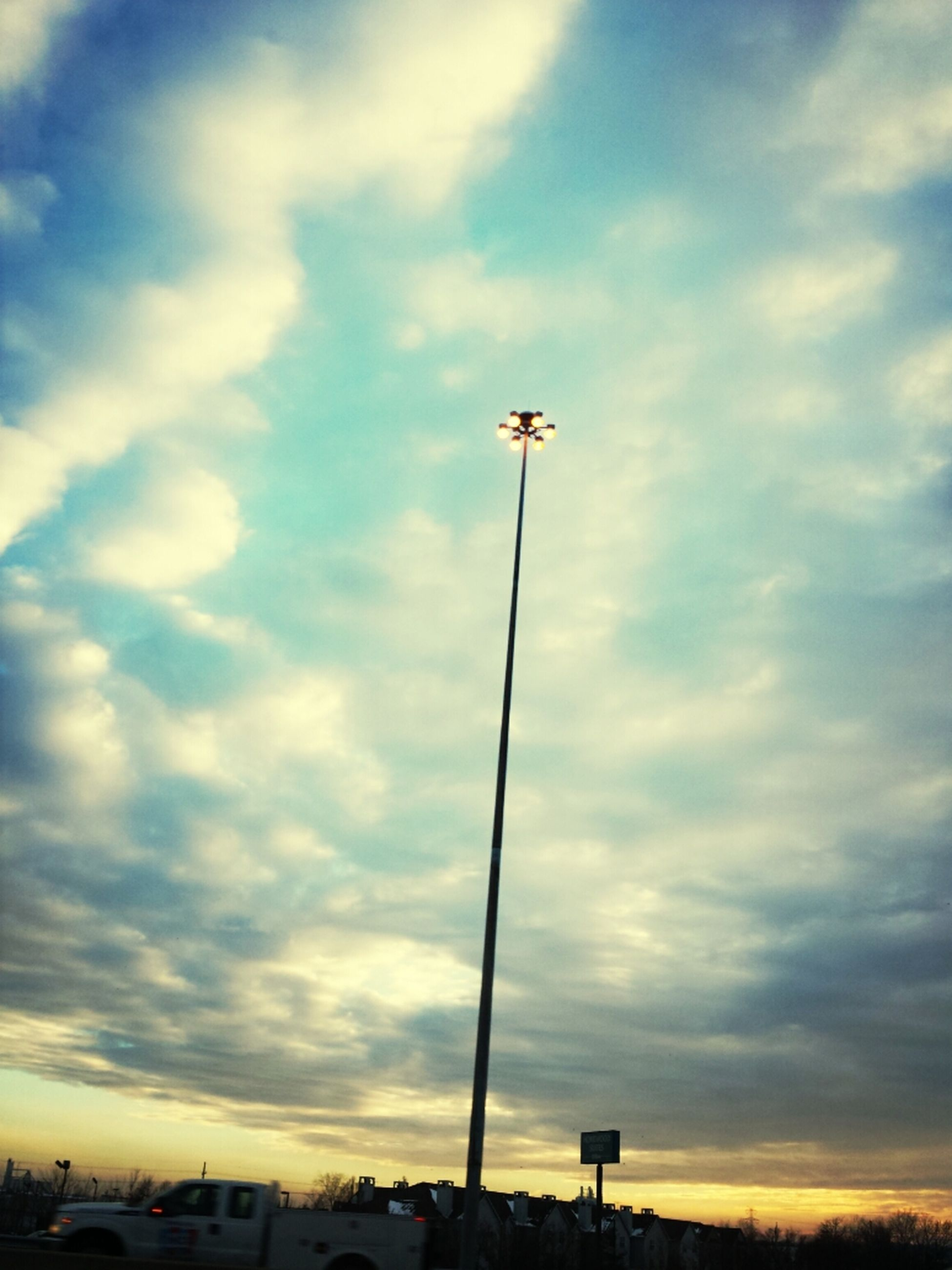 street light, sky, cloud - sky, cloudy, low angle view, transportation, lighting equipment, car, cloud, mode of transport, land vehicle, street, sunset, weather, road, pole, outdoors, silhouette, no people, overcast