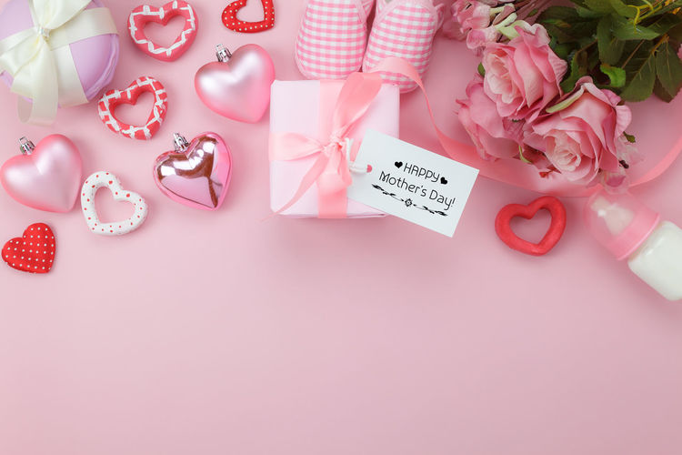 High angle view of gifts and decoration on pink table