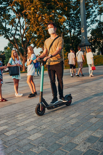 Full length of young man wearing flu mask standing on electric push scooter