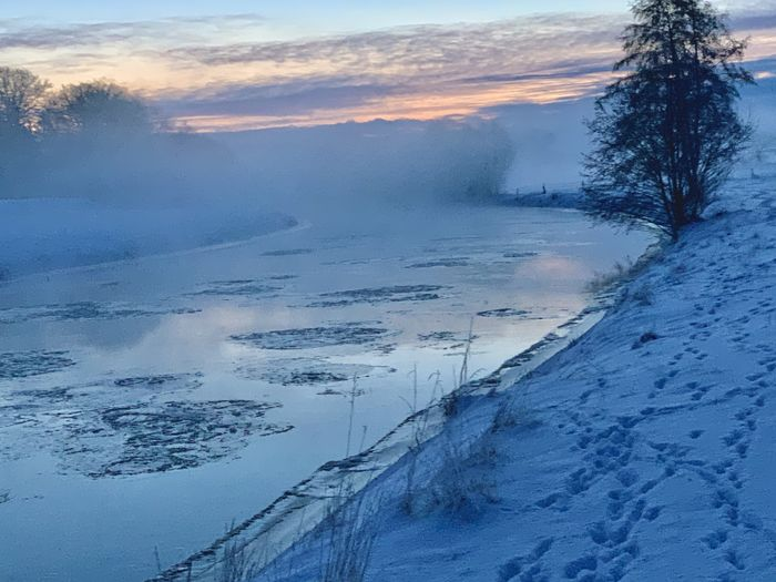 Scenic view of snow covered landscape against sky at sunset