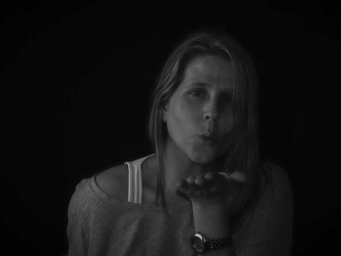 Portrait of woman blowing kiss over black background