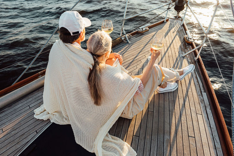 Rear view of couple sitting on boat sailing in sea
