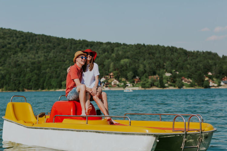 Young lovers having fun in pedalo boat on hot summer day. Cheerful man and woman holding hands while boating on the sea. Boating Couple Date Holiday Horizontal Love Man Romantic Summertime Vacations Woman Young Boat Boyfriend Caucasian Day Girlfriend Lake Outdoors Pedalo Relax Sea Summer Two People Water