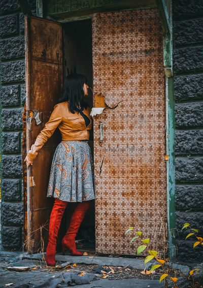 Woman Standing At Door Of Abandoned House