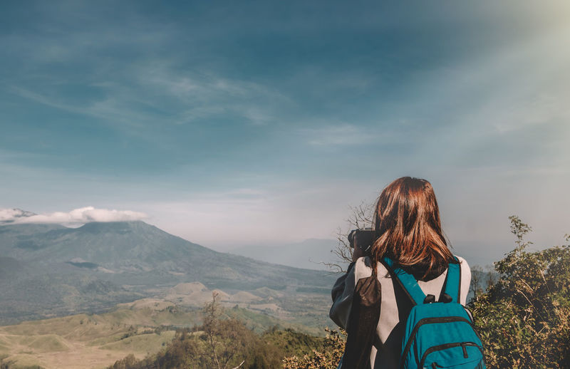 Rear View Of Woman With Backpack Photographing Mountains While Standing Against Sky