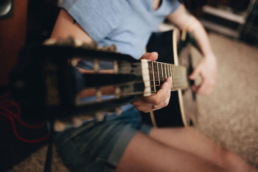 Acoustic Guitar Arts Culture And Entertainment Close-up Day Electric Guitar Fretboard Guitar Holding Human Hand Indoors  Leisure Activity Lifestyles Men Midsection Music Musical Instrument Musical Instrument String Musician Playing Plucking An Instrument Real People Sitting Skill  Technology Two People