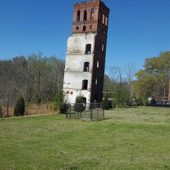 Textile mill Shadow Tower Tree Clear Sky Outdoors Archival Built Structure Sky Day Grass No People Architecture From The War Long Gone  Textile Mill No Filter, No Edit, Just Photography Nature Backgrounds Exploring Historical Monuments Memorial Architecture War History Monument