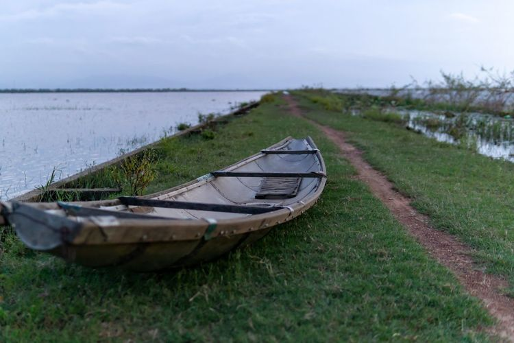 Prepare for flood. Grass Water Transportation Nautical Vessel Land Nature Mode Of Transportation Tranquility Moored Sky No People Tranquil Scene Day Scenics - Nature Abandoned Outdoors Field Rowboat Boat Selective Focus Lakeside Rural Scene Rural Countryside