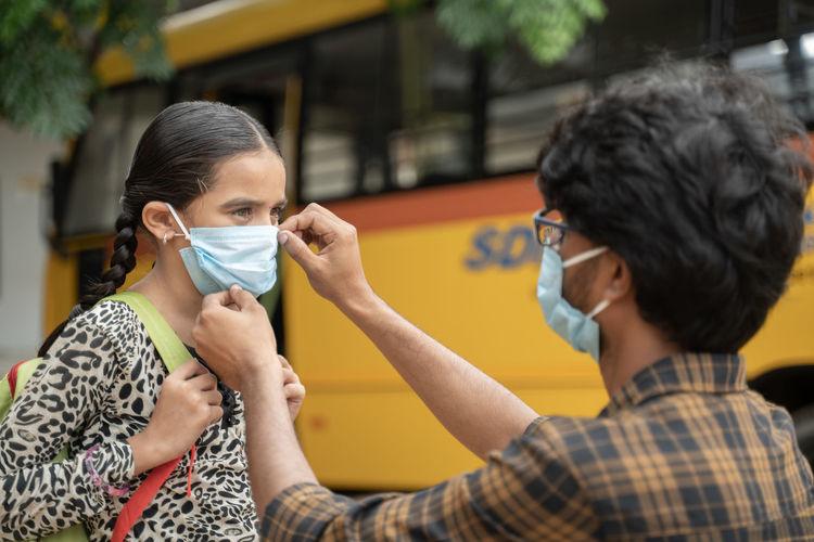 Man holding mask of girl