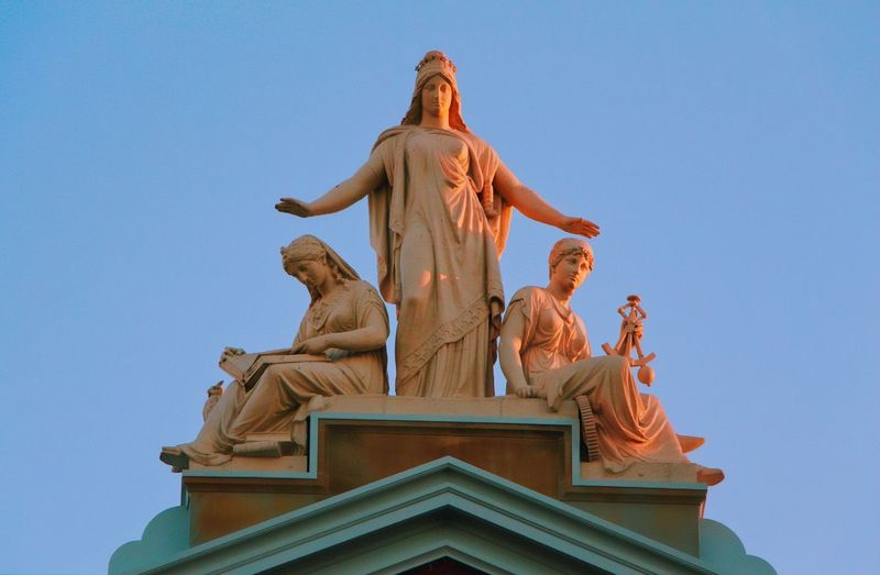 Low Angle View Of Statues On Top Of Museum Against Clear Blue Sky