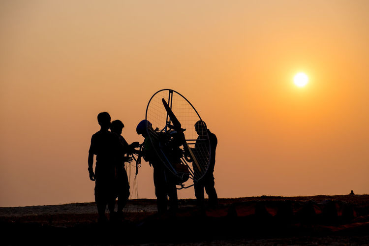 Silhouette People With Paragliding Equipment Against Clear Sky During Sunset