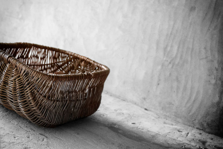 Close-up of empty basket on floor against wall