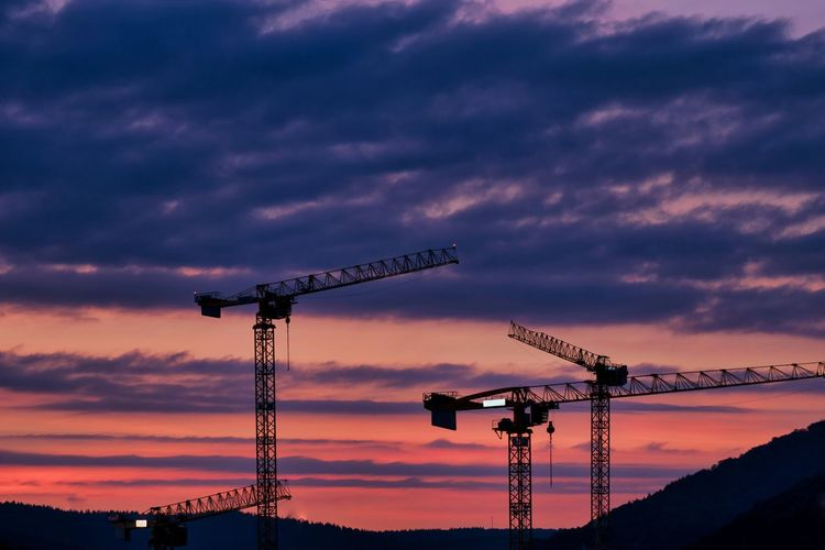 Low angle view of silhouette cranes against sky at sunset
