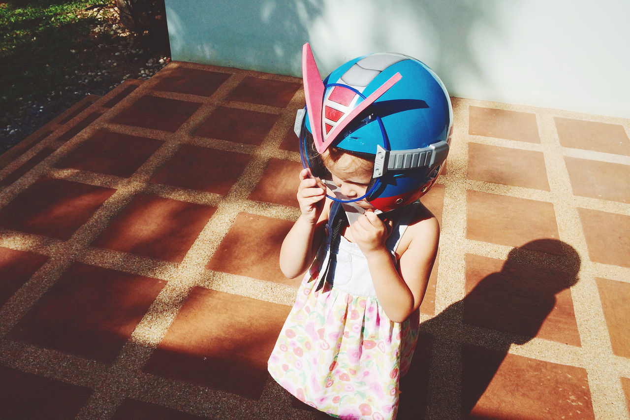Close-up of cute girl wearing helmet while standing at yard