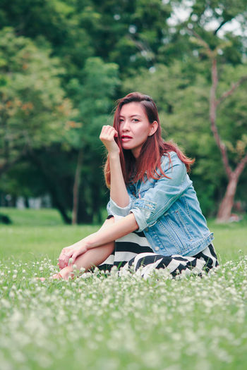 Portrait of a young woman sitting on field