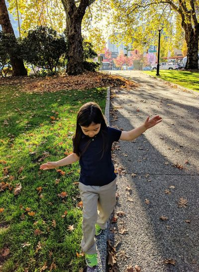 Full length of child standing by tree during autumn