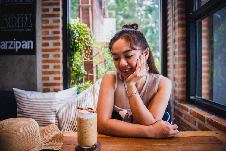 Young woman looking away while sitting on table at cafe
