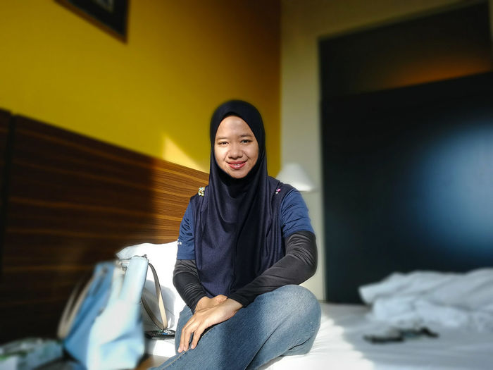 Portrait of smiling woman wearing hijab while sitting on bed