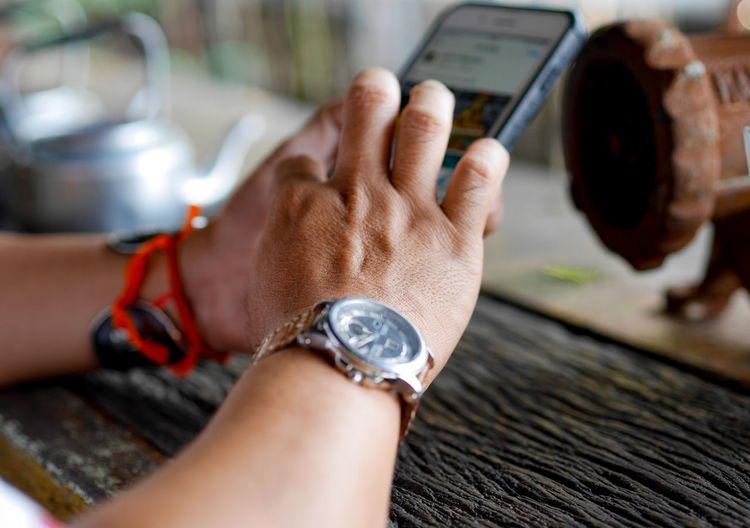 Close-up of man hands holding mobile phone on table