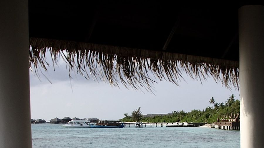 View from Jetty on Maldivian Island Architectural Feature Architecture Beach Beauty In Nature Boat Dhoni Jetty Nature Nautical Vessel Outdoors Palm Trees Part Of Pier Scenics Sea Summer Thatched Roof Tranquil Scene Travel Tree Turquoise Water Vacations Water Watervillage Window