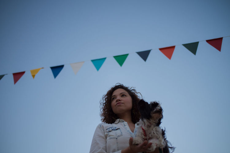 Low angle view of woman holding dog against clear blue sky