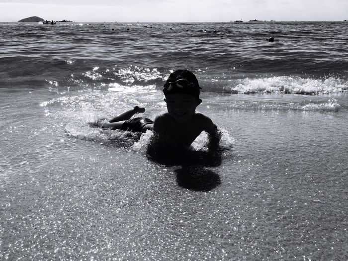 Boy lying on front at beach