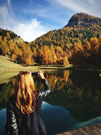 Rear view of woman photographing lake against mountain