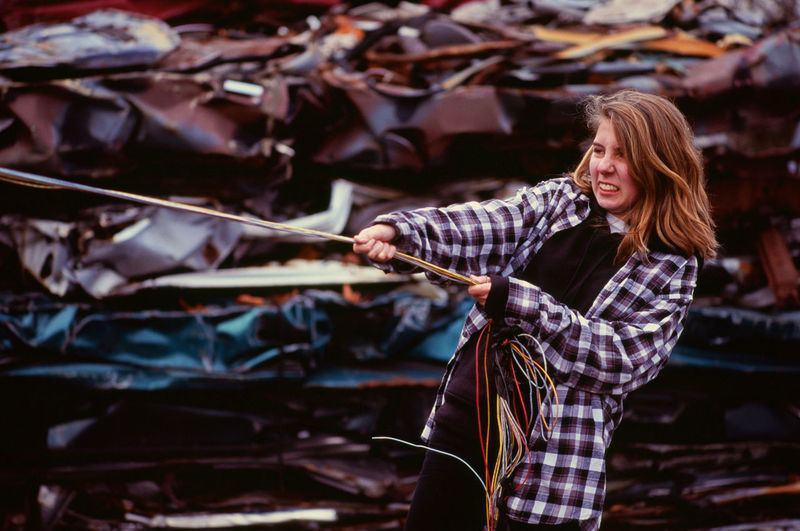 Young woman pulling on wires in an auto salvage yard