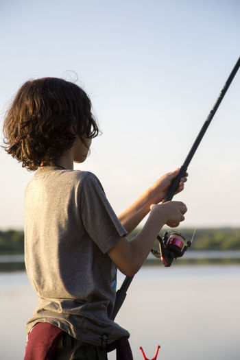 Boy Fishing By Lake Against Clear Sky