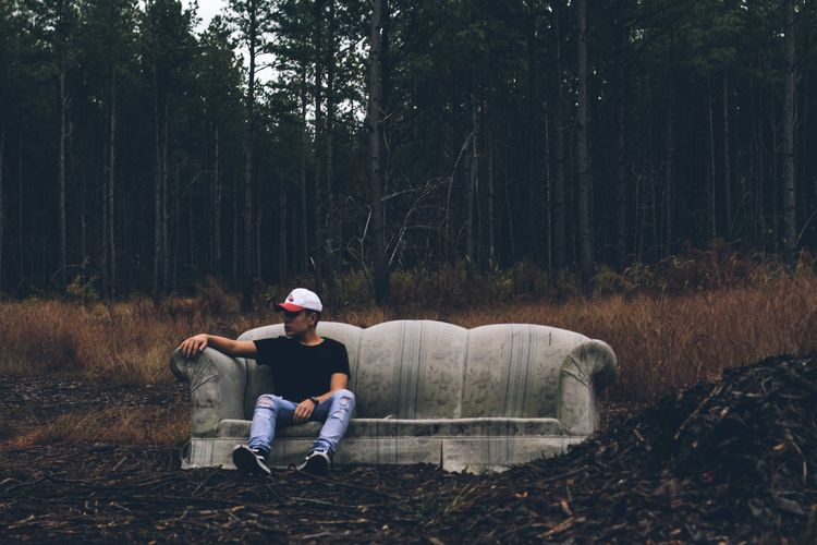 Man sitting on sofa in forest