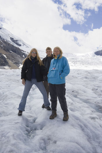 Portrait Of Woman With Kids Standing At Athabasca Glacier In Jasper National Park Against Sky