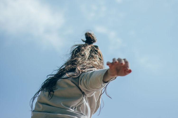 Woman dancing against sky