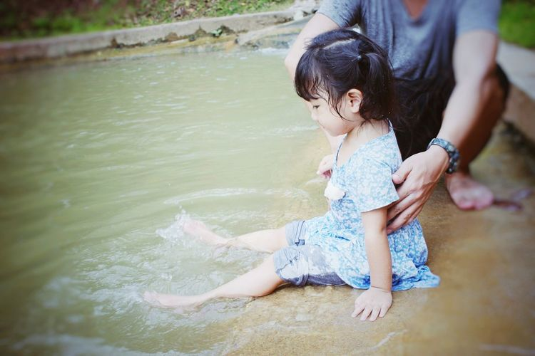 Low Section Of Father Holding Daughter Playing In River
