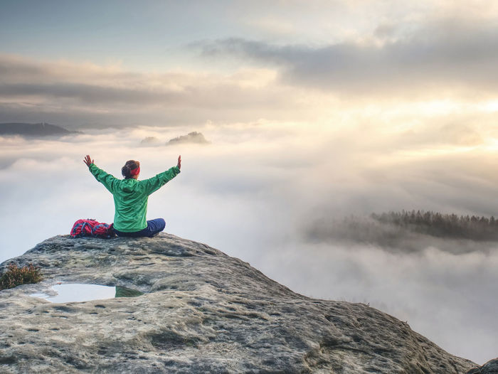 Girl sits with raised hands on against sunrise with thick mist and celebrate start of amazing day