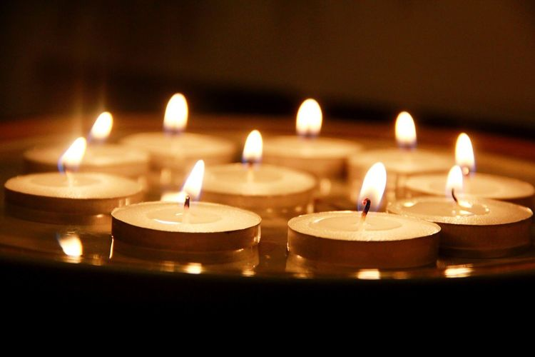 Close-up of lit candles against blurred background