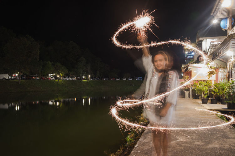 Blurred Motion Sparkler Arts Culture And Entertainment Casual Clothing Architecture Leisure Activity Glowing Long Exposure Water Three Quarter Length Night Standing Real People Illuminated One Person Outdoors Lifestyles Firework Display Nature Firework Motion