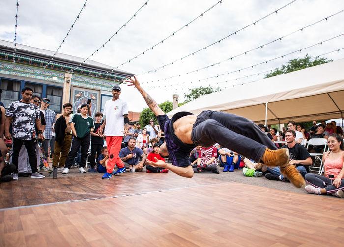 Group of people dancing against sky