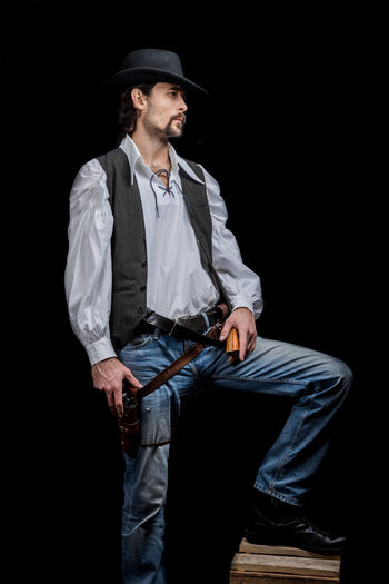 Handsome young man. This is an American cowboy. A vow to a white shirt, brown waistcoat and blue jeans. Black shoes on the feet. Carries a shtyapa, on a belt two pistols. The hair is of medium length; on the face is a beard and mustache. Authentic photo. Culture of America. Cowboy Wild West America American Gun National Authentic Moments Lifestyles Lifestyle One Person Candid Authentic Three Quarter Length Clothing Hat Front View Young Men Men Young Adult Black Background Holding Looking Away Real People Males  Standing