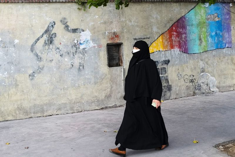 Rear view of woman standing against graffiti wall
